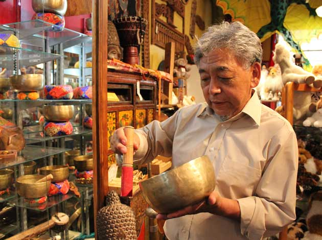 Heart of Tibet co-owner Thupten Dadak demonstrates a singing bowl, one of many authentic pieces at the shop. Photo by Michelle Bruch