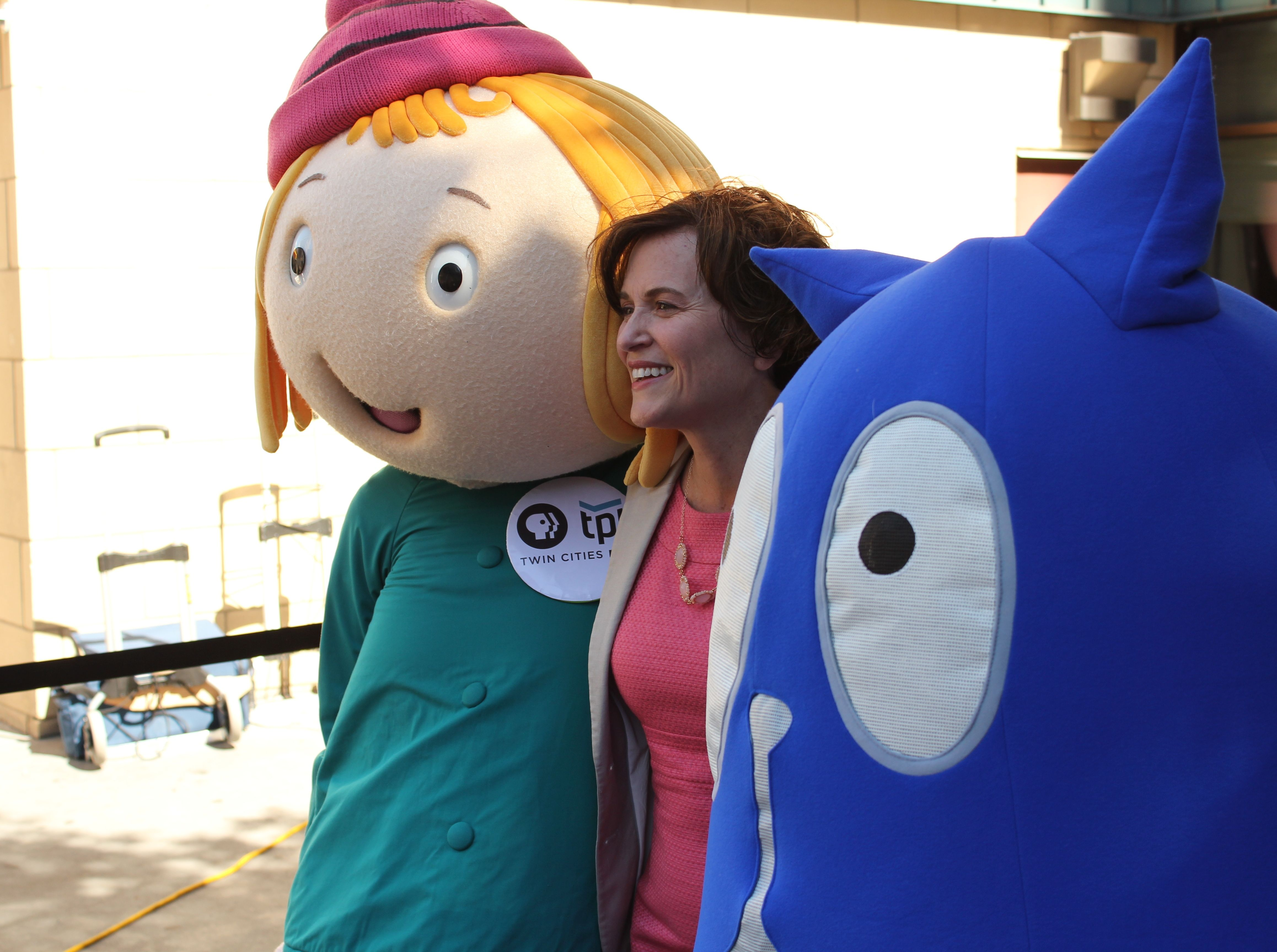 "Mayor Betsy Hodges poses with costumed actors portraying the stars of the ""Peg + Cat"" children's television show."