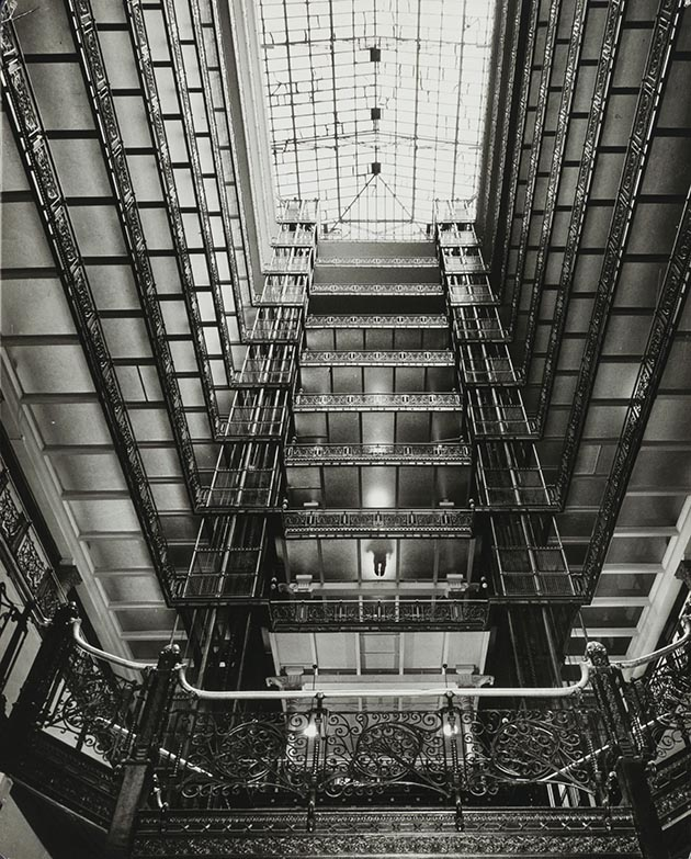 View from bottom of the Metropolitan Building's light court, 1961. The 56-by-90-foot court, with its superb ironwork and glass-floored galleries, was one of the supreme spaces of its kind in the history of American architecture. The ghostly figure on the fourth floor is one of the building's janitors. Credit: Minnesota Historical Society.