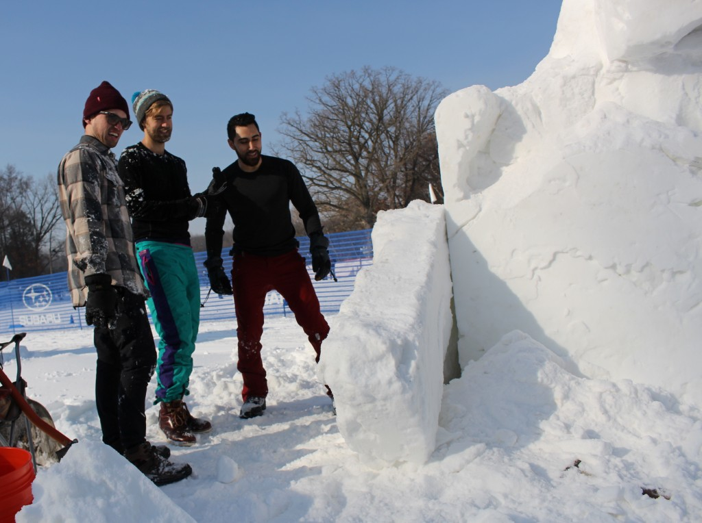 """Tyler Govek, Dallas Erdahl and Thomas Bales (from left to right) create a snow sculpture during the Southwest Journal snow sculpture contest Feb. 2 at Theodore Wirth Park. The team created a sculpture of an octopus called """"Frozen Fingers."""" Photo by Nate Gotlieb"""